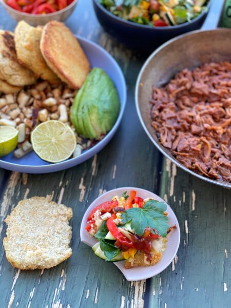 Arepas Maisfladen mit Pulled Pork, Avocado und Salat Füllung, Zutaten in Schalen auf Tisch