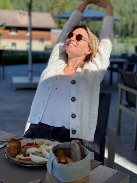 Frau beim Frühstück streckt Arme in die Luft