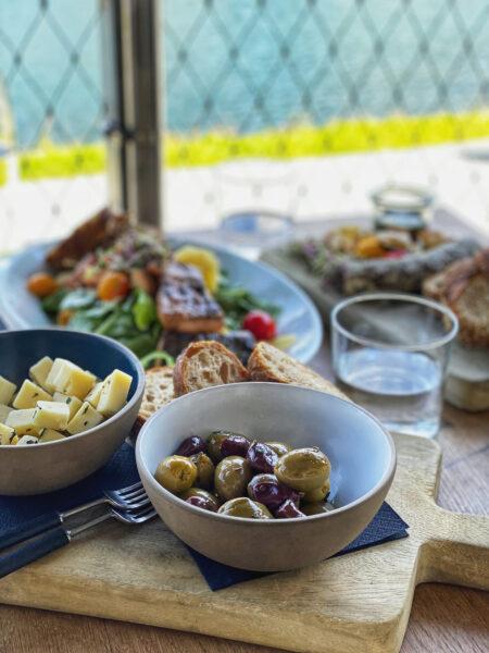 Oliven, Käse, Essen auf Tisch mit Blick auf See