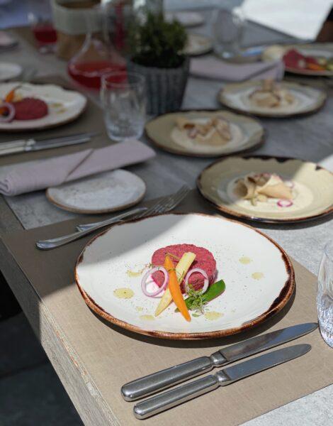 Tatar auf Teller angerichtet, gedeckter Tisch, Kochkurs Mittagessen Hotel Valsana
