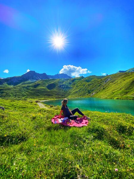 Frau sitzt am Schwellisee in Arosa Schweiz, blauer Himmel und Sonne