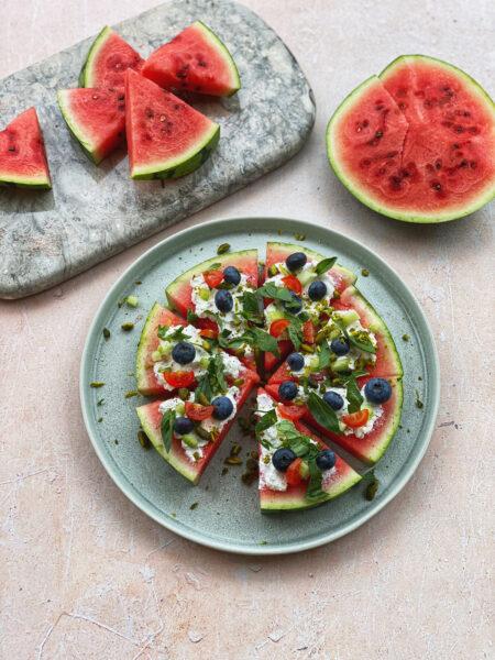 Wassermelonen Pizza mit Ziegenfrischkäse und Tomaten garniert, Wassermelonenstückchen