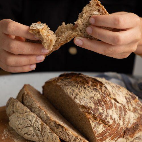 Ruchbrot angeschnitten, hände ziehen Brot auseinander
