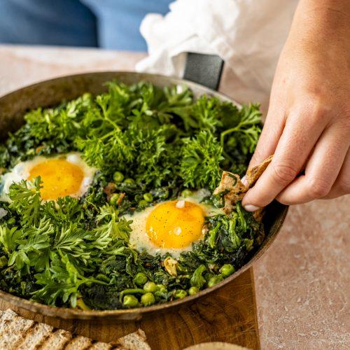Grünes Shakshuka in der Pfanne, Spinat, Eier, Fladenbrot
