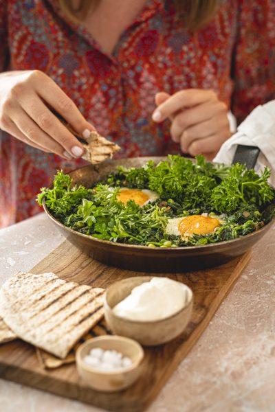 Grünes Shakshuka in der Pfanne, Spinat, Eier, Fladenbrot, Hand