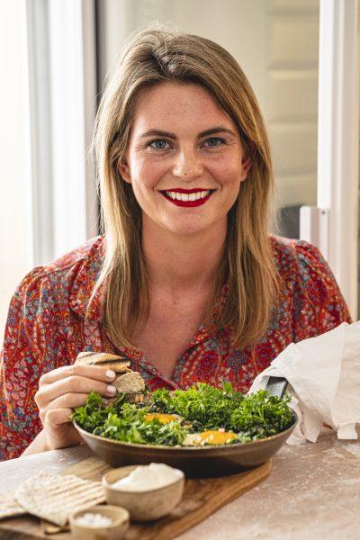 Grünes Shakshuka in der Pfanne, Spinat, Eier, Fladenbrot, Frau essend