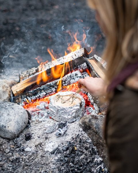 Vacherin im Alufolie über offenem Feuer, Glut, Lagerfeuer, Frau von hinten